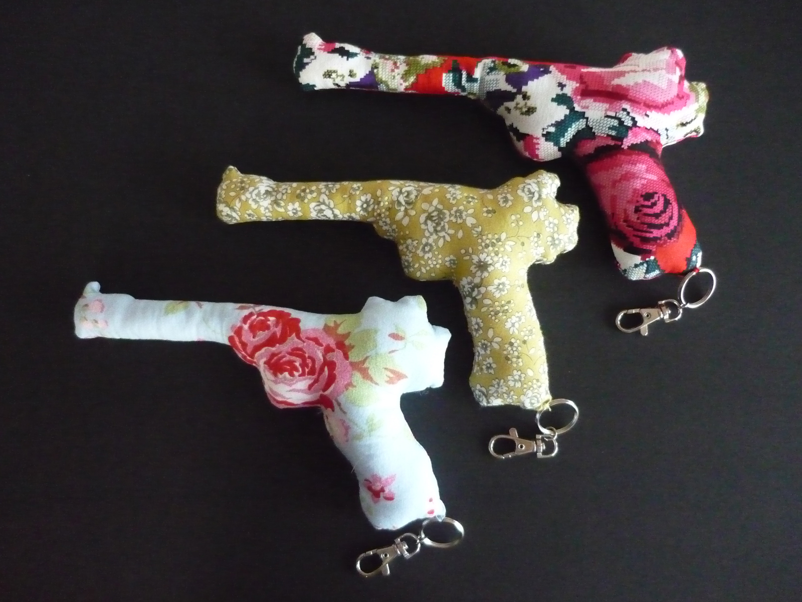 hree flower patterned fabric guns sit on a black background. All three guns have a key chain hanging from the base.