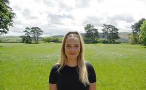 Charlotte stands smiling looking at the camera. She has long blonde hair and a black t-shirt on. She is standing in a lush green field.